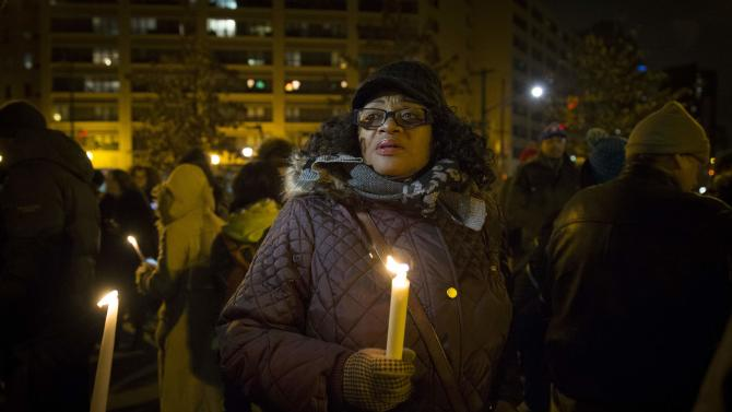 A woman holds a candle as demonstrators gather in Central Park in Harlem