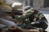 A Syrian rebel aims his rifle during fighting to root out government forces from their positions in the Amariya neighbourhood of Aleppo