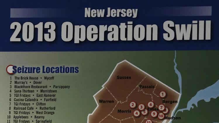 """A map is displayed showing findings in an investigation dubbed """"Operation Swill,"""" in which 29 bars and restaurants in New Jersey are accused of putting cheap booze in premium brand liquor bottles and selling it, during a news conference, Thursday, May 23, 2013, in Trenton, N.J. Thirteen of the restaurants cited are TGI Fridays located in central and northern New Jersey. (AP Photo/Julio Cortez)"""