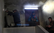 FILE - In this Saturday, Nov. 17, 2012 file photo, a Syrian fighter fires his weapon during clashes with Syrian army forces in town of Harem on the outskirts of Idlib, Syria. Through mid-2012, rebel power grew and Assad&#39;s army ramped up its response. Relentless government shelling leveled neighborhoods and killed hundreds. Regular reports emerged of mass killings by the regime or thugs loyal to it, pushing more Syrians toward armed struggle. The government, which considers the opposition terrorist gangs backed by foreign powers, denied any role, and does not respond to requests for comment on its military. The rebels, too, were accused of atrocities. (AP Photo/ Khalil Hamra, File)