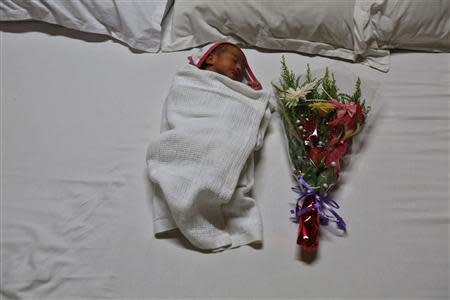 Gabriella, the week-old daughter of Rekha Patel and Daniele Fabbricatore sleeps in a hotel room in Anand town