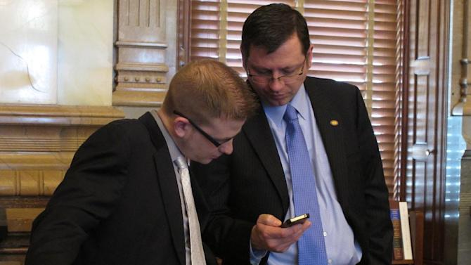 Kansas Senate Majority Leader Terry Bruce, right, a Hutchinson Republican, consults his chief of staff, Peter Northcott, left, before the Senate takes up anti-abortion legislation, Friday, April 5, 2013, at the Statehouse in Topeka, Kan. Bruce supports the bill, which blocks tax breaks for abortion providers and imposes other restrictions. (AP Photo/John Hanna)
