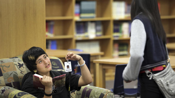 """In this Oct. 1, 2012 photo, Kayla Saucedo, left, shows her ID badge to a fellow student at Anson Jones Middle School in San Antonio, Texas. The San Antonio school district's website was hacked over the weekend to protest its policy requiring students to wear microchip-embedded cards tracking their every move on campus. A teenager purportedly working with the hacker group Anonymous said in an online statement that he took the site down because the Northside school district """"is stripping away the privacy of students in your school."""" All students at John Jay High School and Anson Jones Middle School are required to carry identification cards embedded with a microchip. They are tracked by the dozens of electronic readers installed in the schools' ceiling panels.  (AP Photo/San Antonio Express-News, Bob Owen)   RUMBO DE SAN ANTONIO OUT; NO SALES"""