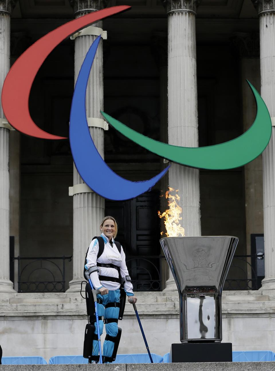 Claire Lomas lstands by  Paralympic flame cauldron  after lighting it in Trafalgar Square in London, Friday, Aug. 24, 2012. Claire had a horse riding accident in 2007 leaving her paralysed from the chest down. The London Paralympics begin on Wednesday Aug. 29. (AP Photo/Kirsty Wigglesworth)