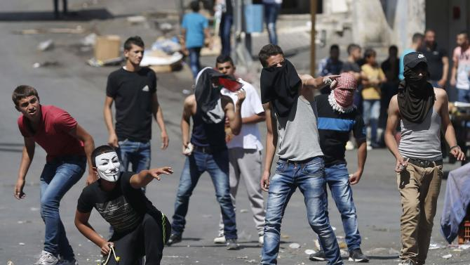Palestinian protesters take position during clashes with Israeli troops following funeral of Palestinian prisoner al-Jaabari in Hebron