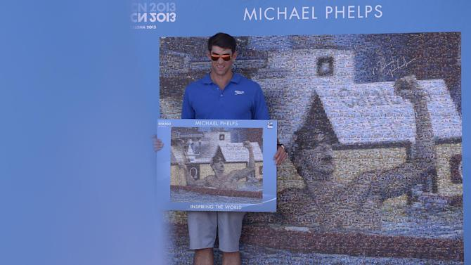 Former Olympic and world swimming champion Michael Phelps of the US unveils a mosaic installed in his honour at the FINA Swimming World Championships in Barcelona, Spain, Sunday, July 28, 2013 .(AP Photo/Manu Fernandez)