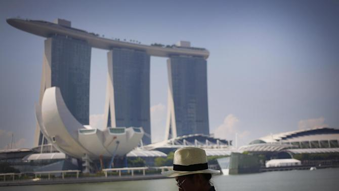 A tourist checks her smart phone after taking pictures of the Marina Bay Sands architecture seen in the background, a popular tourist spot, Tuesday, April 21, 2015, in Singapore. The city-state's government announced earlier in the year, new plans for its global marketing campaign to tap on the country's year-long 50th birthday celebration, as part of its continued effort to boost tourism numbers in 2015, after the country went through a challenging season in 2014.(AP Photo/Wong Maye-E)