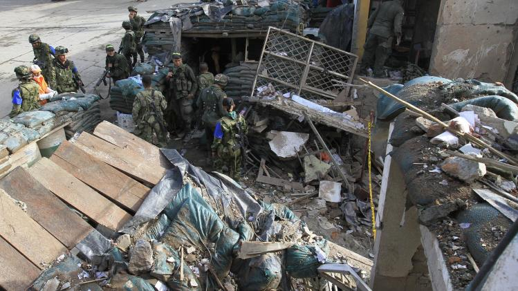 Colombian soldiers stand amid the ruins of a police station that was destroyed in a bomb attack in Inza