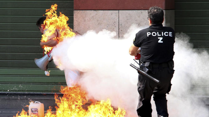 A police officer uses a fire extinguisher as a man sets himself on fire outside a branch of Piraeus bank in the northern port city of Thessaloniki, Greece, Friday Sept. 16, 2011. It was a third attempted self-immolation by the former small business owner, who says he was ruined after taking a series of bank loans. The 56-year-old was hospitalized with non life-threatening chest burns. (AP Photo/Nontas Stlianidis)