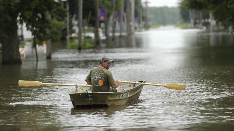 Jim Johnson rows his boat down Main Street, Tuesday, June 25, 2013, in New Hartford, Iowa. Hundreds of residents obeyed an order to evacuate their homes in this northeast Iowa town Tuesday before floodwaters from a rising creek could strand them. (AP Photo/Charlie Neibergall)
