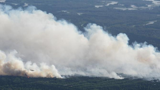 A State Division of Forestry air tanker works the Sockeye fire north of Kashwitna Lake on Sunday, June 14, 2015, near Willow, Alaska. The wildfire north of Anchorage shut down a key highway and forced the evacuation of about 1,700 structures after it mushroomed in size. (Bill Roth /Alaska Dispatch News via AP) MANDATORY CREDIT KTUU-TV OUT; KTVA-TV OUT; THE MAT-SU VALLEY FRONTIERSMAN OUT