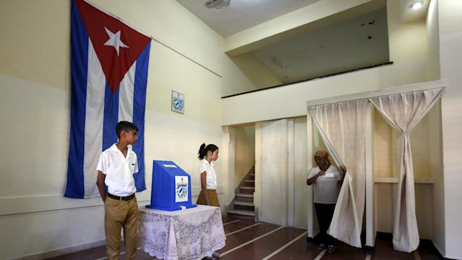 A woman walks out of a voting booth to cast her vote at a polling station at a school in Havana