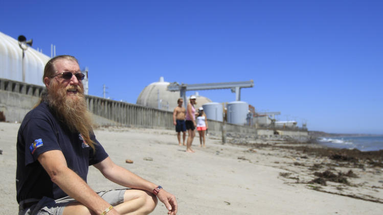 """In this Thursday, June 30, 2011 picture, Bret Gross, a resident of San Clemente, Calif., sits on the beach just outside the San Onofre Nuclear Generating Station, about five miles from his home. He worries that the area cannot be quickly evacuated in a severe nuclear accident. """"Forget the amount of training and plans,"""" he said. """"It'll be ugly."""" (AP Photo/Lenny Ignelzi)"""