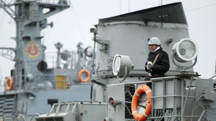 A Ukrainian sailor stands guard on top of a Ukrainian navy ship at the Crimean port of Yevpatorya