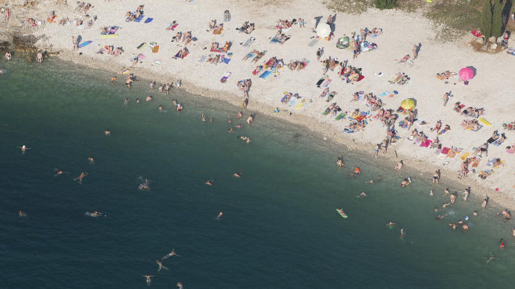 In this aerial photo taken June 17, 2013, tourists enjoy the beach in Pula, northern Adriatic. On Monday July 1, 2013, Croatia will become the 28th EU member, the bloc's first addition since Bulgaria and Romania joined in 2007. Croatia's membership marks a historic turning point for the small country, which went through carnage after declaring independence from the former Yugoslavia in 1991. (AP Photo/Darko Bandic)