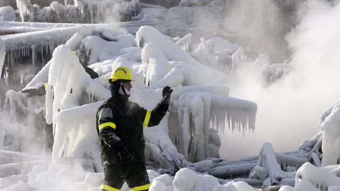 A police investigator signals to colleagues as they search through icy rubble to trying to locate more victims of a fire that destroyed a seniors' residence Friday, Jan. 24, 2014, in L'Isle-Verte, Quebec. Five people are confirmed dead and 30 people are still missing, while with cause of Thursday morning's blaze is unclear police said. Authorities are using steam to melt the ice and to preserve any bodies that are buried. (AP Photo/The Canadian Press, Ryan Remiorz)