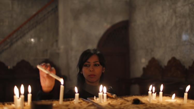 Palestinian Christian lights candles as she attend a service in Saint Porfirios church in Gaza City