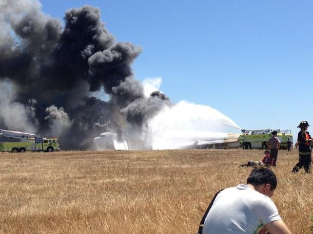 Firefighters are on hand as smoke billows from Asiana Airlines flight 241 (Photo by Wendell Hom)