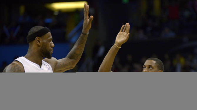 Miami Heat guard Mario Chalmers (15) is congratulated on a basket by forward LeBron James (6) during the second half of an NBA basketball game against the Orlando Magic in Orlando, Fla., Monday, March 25, 2013. The Heat won 108-94. (AP Photo/Phelan M. Ebenhack)