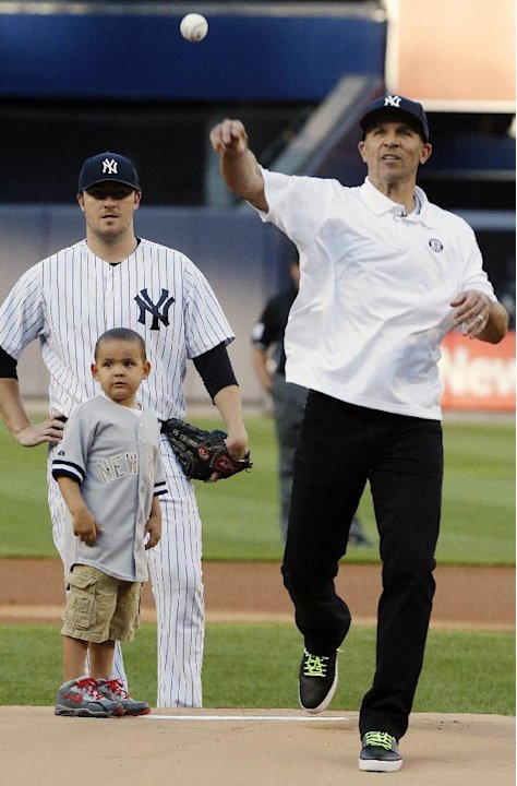 Brooklyn Nets NBA basketball head coach Jason Kidd throws out the ceremonial first pitch as his son, Chance, left, and New York Yankees starting pitcher Phil Hughes, watch before the second baseball g
