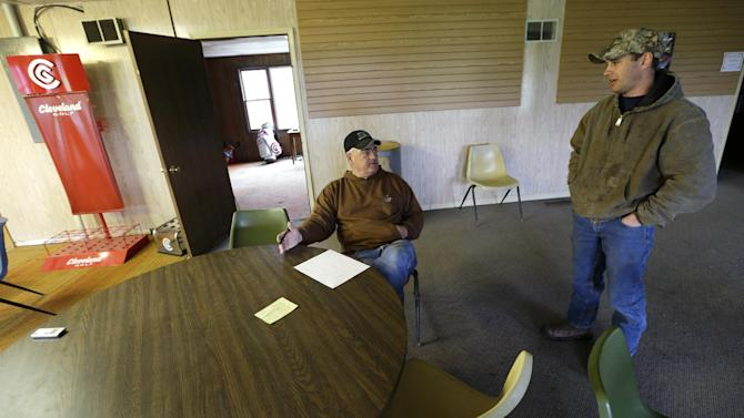 In this Wednesday, April 10, 2013 photo, farmer Clark Kelly talks with his son-in-law Brandon Priesman, right, in the clubhouse at the Hend-Co-Hills Golf Course, in Biggsville, Ill. Kelly purchased the course, which was in foreclosure, with plans to plow it into farm land. Across the Midwest, farmers are planting crops on almost any scrap of available land to take advantage of consistently high corn and soybean prices. (AP Photo/Charlie Neibergall)