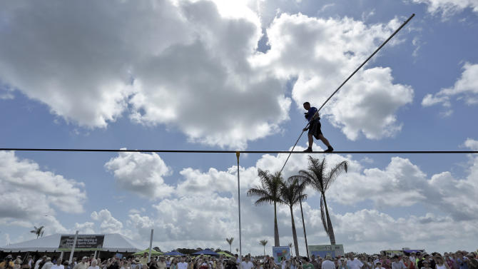A large crowd watches as high wire performer Nik Wallenda walks across a wire as he practices Tuesday, June 18, 2013 in Sarasota, Fla. Wallenda, a seventh generation high-wire walker, will attempt to walk across the Grand Canyon on Sunday, June 23, 2013. (AP Photo/Chris O'Meara)