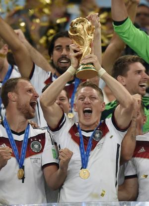 Germany's Bastian Schweinsteiger raises the trophy after the World Cup final soccer match between Germany and Argentina at the Maracana Stadium in Rio de Janeiro, Brazil, Sunday, July 13, 2014. Germany won the match 1-0. (AP Photo/Martin Meissner)