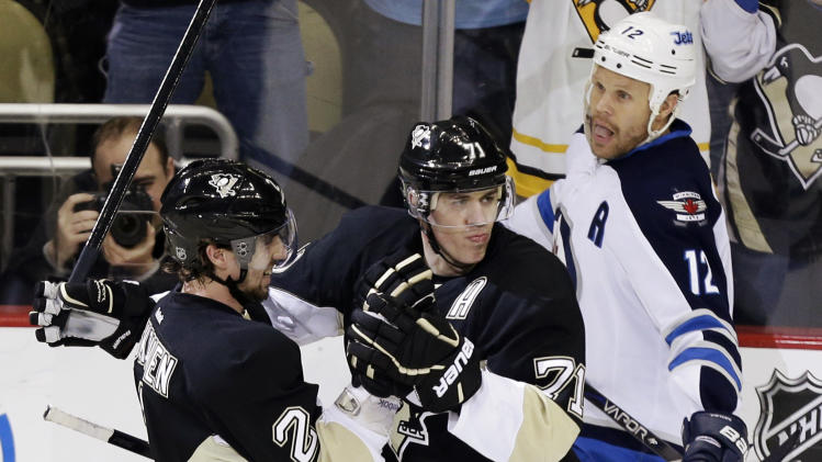 Pittsburgh Penguins center Evgeni Malkin (71) celebrates his first-period goal with defenseman Matt Niskanen (2) as Winnipeg Jets center Olli Jokinen (12) skates back to his bench during an NHL hockey game in Pittsburgh, Thursday, March 28, 2013. (AP Photo/Gene J. Puskar)