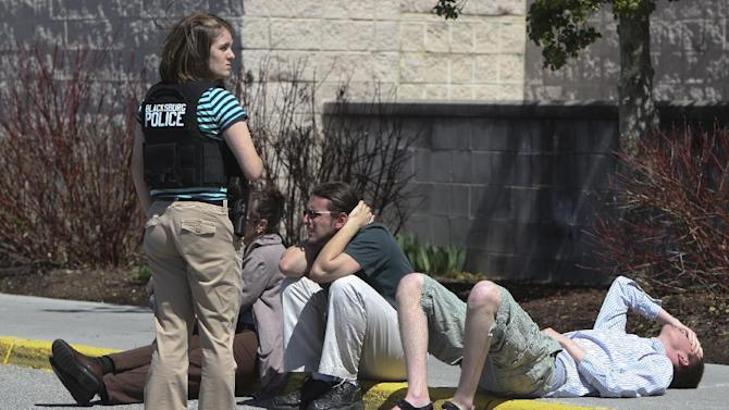 A police officer stands guard next to people on a curb outside the New River Valley Mall in Christiansburg, Va. on Friday, April 12, 2013. Officials say two women have been shot at the community college section of the mall and a suspect is in custody. (AP Photo/The Roanoke Times, Daniel Lin)