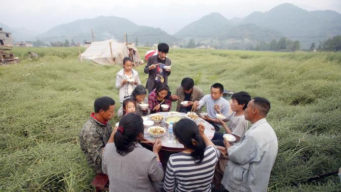 Villagers gather for a meal outdoor in the quake struck Lushan county in southwestern China's Sichuan province Monday, April 22, 2013. The efforts under way in the mountainous province after a quake Saturday that killed nearly 200 people showed that the government has continued to hone its disaster reaction — long considered a crucial leadership test in China — since a much more devastating earthquake in 2008, also in Sichuan, and another one in 2010 in the western region of Yushu. (AP Photo) CHINA OUT