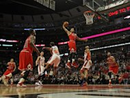 Derrick Rose of the Chicago Bulls goes up for a dunk between Baron Davis and Tyson Chandler of the New York Knicks on his way to a game-high 32 points at the United Center on March 12, 2012 in Chicago, Illinois. The Bulls defeated the Knicks 104-99