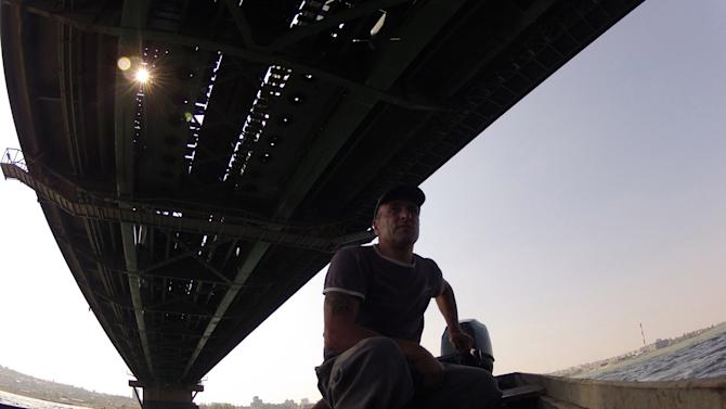 In this photo taken Sept. 18, 2012, fisherman Renato Grbic steers his boat under the Pancevo Bridge over the Danube river in Belgrade, Serbia. Grbic has saved the lives of 25 people who attempted to kill themselves by jumping from a nearby bridge. Over the years, Grbic has rescued people of all ages, social background and gender. There were young girls, middle-aged women, younger or older men. (AP Photo/Darko Vojinovic)