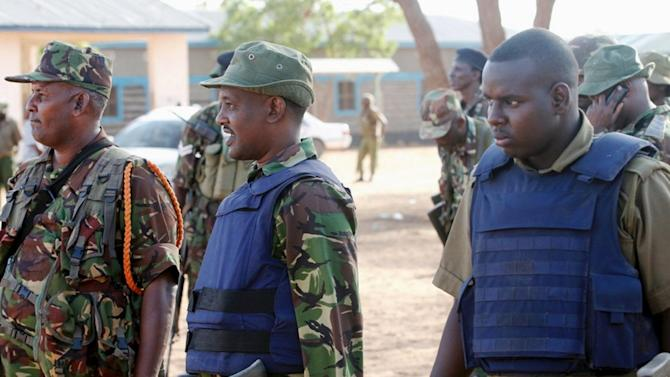 Kenya Defence Forces soldiers and policemen gather at the scene of an overnight attack on a residential complex in Soko Mbuzi village of Mandera town at the Kenya-Somalia border