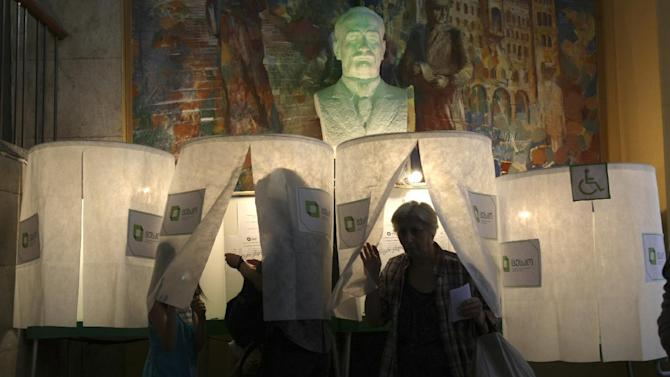 Georgians vote during Parliamentary Election at a polling station in Tbilisi, Georgia, Monday, Oct. 1, 2012, overlooked by a bust of Georgian scientist mathematician Nikoloz (Niko) Muskhelishvili.  Voters in Georgia are voting in a heated parliamentary election Monday that will decide the future of Saakashvili's government. (AP Photo/Shakh Aivazov)
