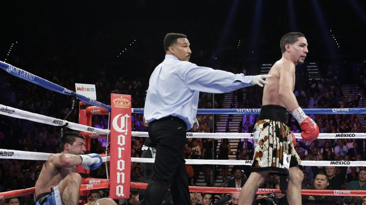 Referee Tony Weeks sends Danny Garcia to his corner before giving Lucas Matthysse a standing eight count during a WBC and WBA super lightweight title fight, Saturday, Sept. 14, 2013, in Las Vegas. (AP Photo/Eric Jamison)