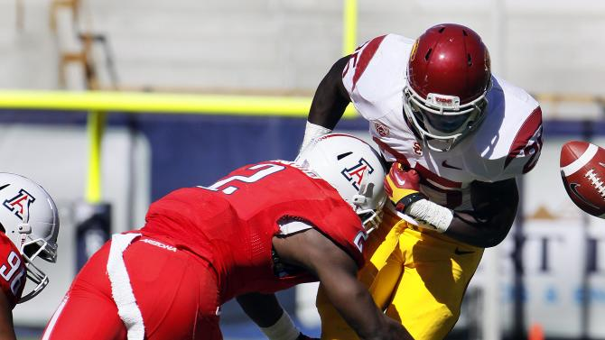 Southern California's Silas Redd (25) loses the ball from a tackle by Arizona's Marquis Flowers (2) during the first half of an NCAA college football game at Arizona Stadium in Tucson, Ariz., Sat., Oct. 27, 2012. (AP Photo/Wily Low)