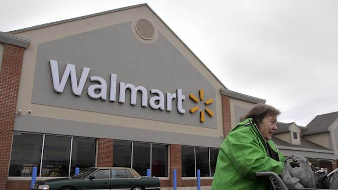 In this Tuesday, Nov. 13, 2012 photo a woman pushes a shopping cart away from the entrance of a Walmart store in North Kingstown, R.I.Wal-Mart Stores Inc. is reporting a 9 percent increase Thursday Nov. 15, 2012 in third-quarter net income as the world's largest retailer continues to woo back shoppers by reemphasizing that it has the lowest prices. (AP Photo/Steven Senne)