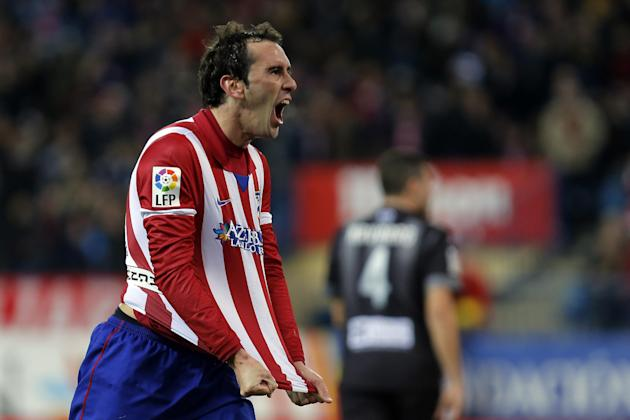 Atletico's Diego Godin, left, celebrates his goal during a Spanish La Liga soccer match between Atletico de Madrid and Levante at the Vicente Calderon stadium in Madrid, Spain, Saturday, Dec. 21,