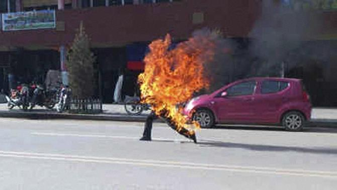 XIAHE: In this photo taken Tuesday, Oct 23, 2012 and released by London-based rights group Freetibet.org, Dorje Rinchen, a farmer in his late 50s, runs after setting himself on fire on the main street in Xiahe in northwestern China's Gansu province. This was the second self-immolation death in two days near the Labrang monastery in Xiahe. The monastery is one of the most important outside of Tibet and was the site of numerous protests by monks following deadly ethnic riots in Tibet in 2008 that were the most sustained Tibetan uprising against Chinese rule in decades. AP/PTI (AP10_24_2012_000103B)
