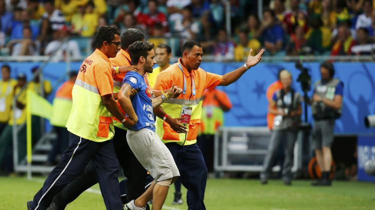 A pitch invader is escorted away by stewards during the 2014 World Cup round of 16 game between Belgium and the U.S. at the Fonte Nova arena in Salvador