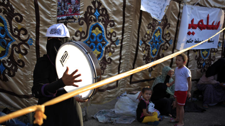 "A Supporter of Egypt's ousted President Mohammed Morsi plays drum during a protest outside Rabaah al-Adawiya mosque, where protesters have installed a camp and hold daily rallies at Nasr City in Cairo, Egypt, Thursday, Aug. 1, 2013. Arabic writing on the banner on the right side reads, ""Peaceful."" (AP Photo/Khalil Hamra)"