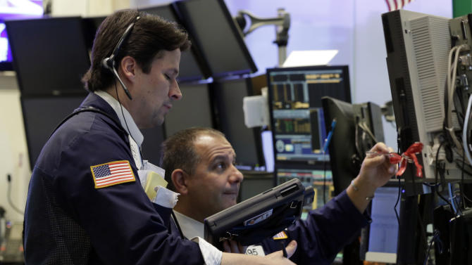 """In this Friday, Dec. 14, 2012,  photo, Traders Patrick McKeon, left, and Joel Lucchese work on the floor of the New York Stock Exchange. Stocks rose modestly Monday, Dec. 17, 2012, on Wall Street. Investors were encouraged by signs of progress in talks to avoid the """"fiscal cliff"""" of tax increases and government spending cuts set to take effect in two weeks and a prediction of steady economic growth next year. (AP Photo/Richard Drew)"""