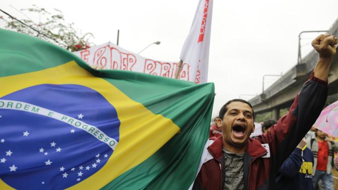 A protester shouts slogans as he helps carry a Brazilian flag in the Capao Redondo neighborhood of Sao Paulo, Brazil, Tuesday, June 25, 2013. Protesters on Tuesday returned to the streets in low-income suburbs of Brazil's biggest city to demand better education, transport and health services, one day after President Dilma Rousseff proposed a wide range of actions to reform Brazil's political system and services. (AP Photo/Nelson Antoine)