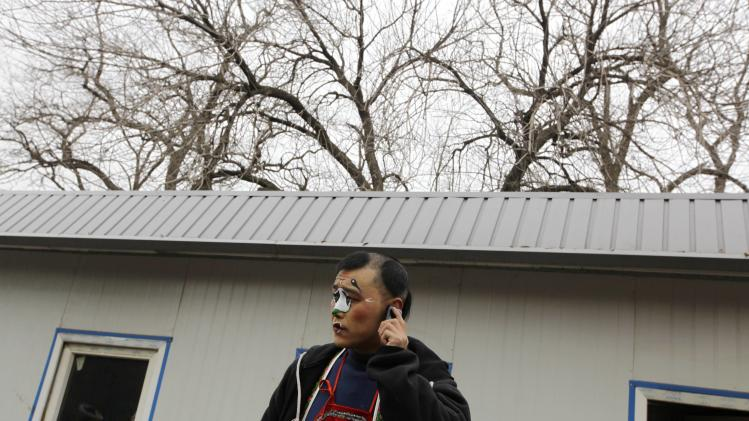 A folk artist uses his mobile phone as he waits for a performance in Beijing