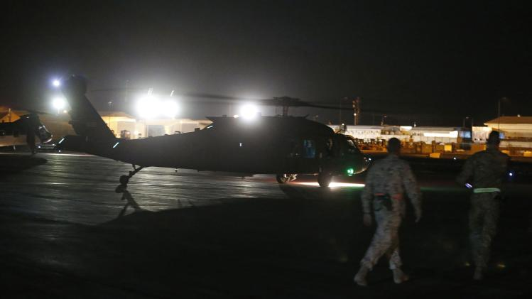 U.S. Military personnel walk past as U.S. Secretary of State John Kerry's helicopter taxis for takeoff in Kabul