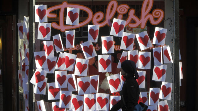 FILE - This Feb. 14, 2012 file photo shows a pedestrian walking past valentines posted on a storefront in Montpelier, Vt. As Valentine's Day approaches, a new poll suggests Cupid's arrow hit the target for most Americans. The Associated Press-WE tv survey finds 66 percent of paired-off adults feel their relationships are perfect or nearly so, and just 3 percent think their partnerships have serious problems. All told, 68 percent of Americans are in committed relationships of some kind, and another 11 percent aren't currently coupled, but would like to be. Seventeen percent say they aren't seeking a relationship. (AP Photo/Toby Talbot, File)