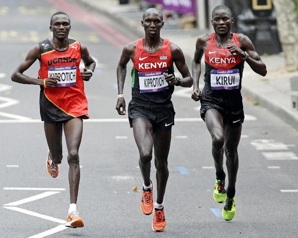 Gold-medalist Stephen Kiprotich of Uganda, left, competes with Kenya's bronze-medalist Wilson Kipsang Kiprotich, center, and silver-medalist Abel Kirui in the men's marathon at the 2012 Summer Olympics, Sunday, Aug. 12, 2012, in London. (AP Photo/Mike Groll)