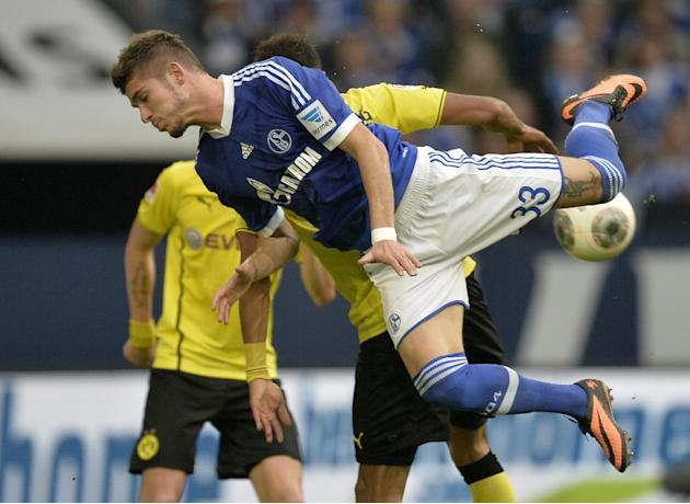 Schalke's Roman Neustaedter jumps for the ball during the German  Bundesliga soccer  match between FC Schalke 04 and Borussia Dortmund in Gelsenkirchen, Germany, Saturday, Oct. 26, 2013