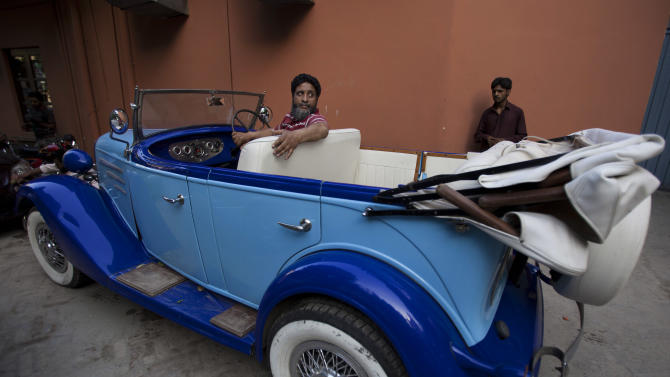 In this photo taken April 22, 2015, a man drives his restored vintage Chevrolet classic car in Rawalpindi, Pakistan. For an elite but passionate group of vintage car collectors in Pakistan, restoring antique rides is like traveling back in time. Mohsin Ikraam, president of the Vintage and Classic Car Club of Pakistan says among rich Pakistanis, the desire to own a classic automobile has been growing and the club's membership has topped 10,000. (AP Photo/B.K. Bangash)