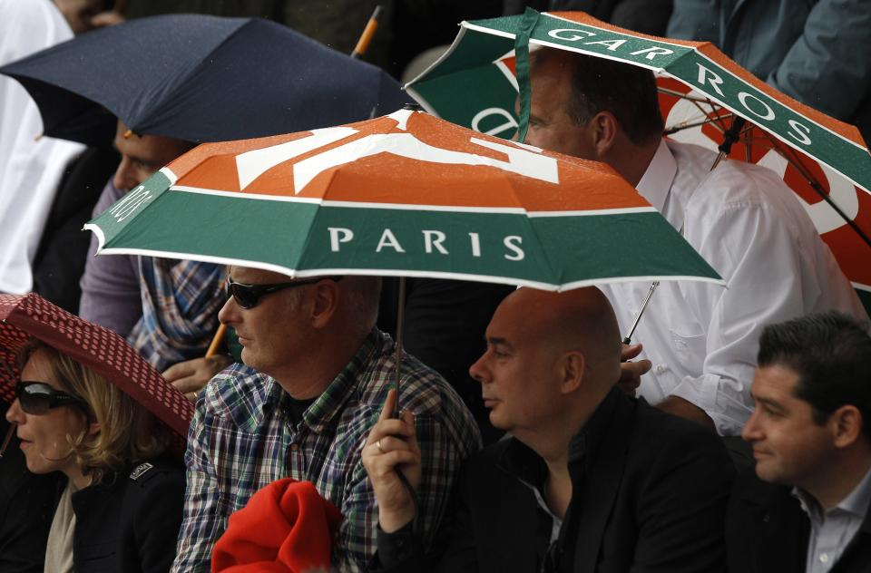 Spectators shield under umbrellas as they watch Czech Republic's Petra Kvitova playing Kazakhstan's Yaroslava Shvedova during their quarterfinal match in the French Open tennis tournament at the Roland Garros stadium in Paris, Wednesday, June 6, 2012.  (AP Photo/Michel Spingler)